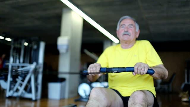 Senior man rowing at the gym