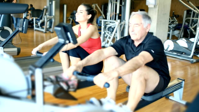 Senior man rowing at the gym with his instructor