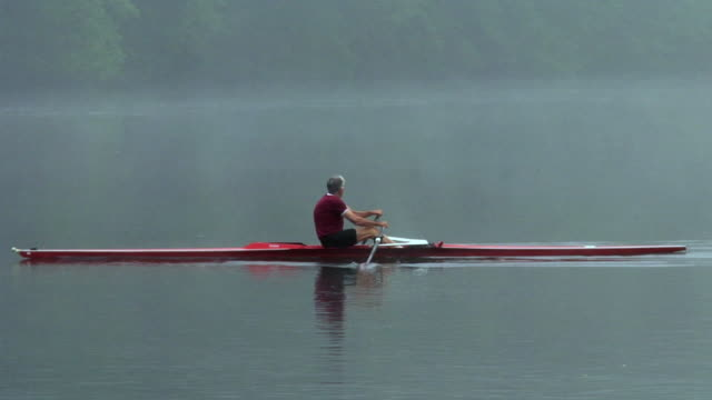 ws pan zi zo senior man rowing in single scull on the connecticut river at dawn/ hanover, new hampshire, usa - sideways glance stock videos & royalty-free footage