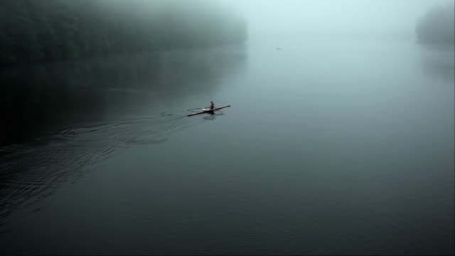 ha ws senior man rowing past in single scull on the connecticut river at dawn/hanover, new hampshire, usa - rudern stock-videos und b-roll-filmmaterial