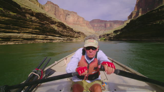 vídeos de stock, filmes e b-roll de ms pov senior man rowing raft down grand canyon / grand canyon, arizona, usa  - feito pelo homem