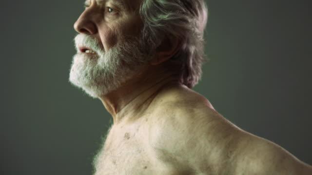 SLO MO CU TU TD Senior man rubbing his back in studio / New York City, New York State, USA