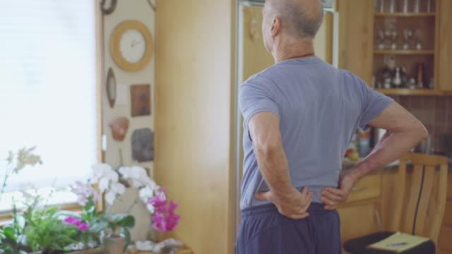 senior man rubbing his lower back - menschliches nervensystem stock-videos und b-roll-filmmaterial