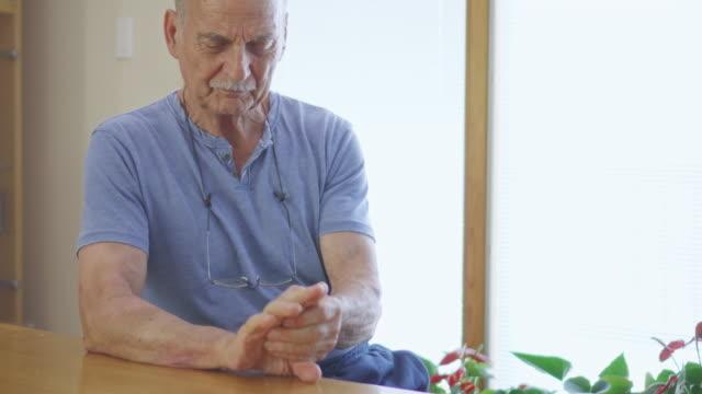vídeos de stock e filmes b-roll de senior man rubbing his painful hands - artrite