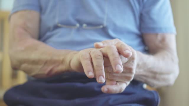 vídeos de stock e filmes b-roll de senior man rubs painful hands - artrite