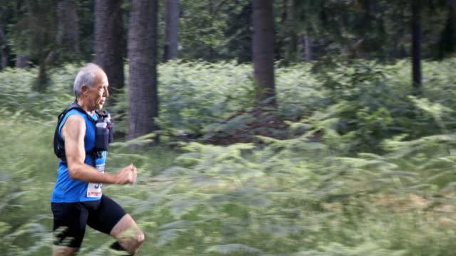 SLO MO DS Senior man een marathon lopen door het bos