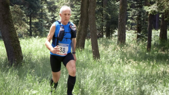 SLO MO DS uomo anziano correre una maratona attraverso la foresta