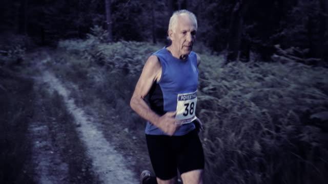 SLO MO DS Senior man running a trail marathon at sunset