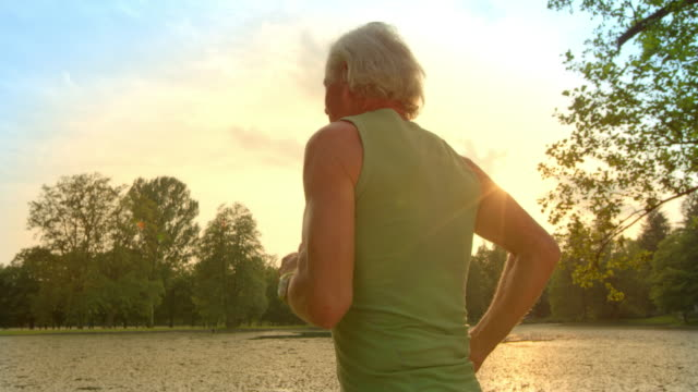 SLO MO TS Senior man running along lake at sunset