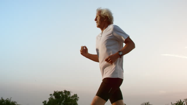 slo mo ts senior uomo che corre al tramonto - sport video stock e b–roll