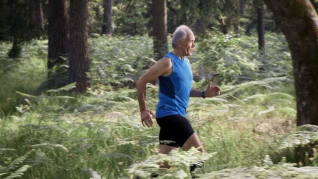 slo mo ds senior man running in the forest - vest stock videos & royalty-free footage
