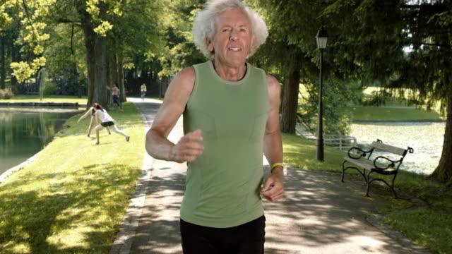 SLO MO TS Senior man running through park in sunshine