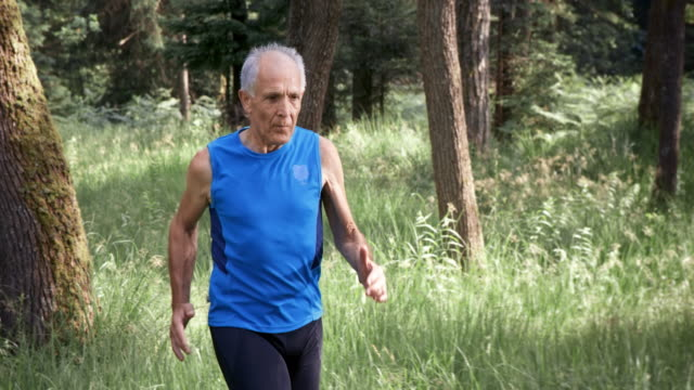 slo mo senior man running through the forest - vest stock videos & royalty-free footage