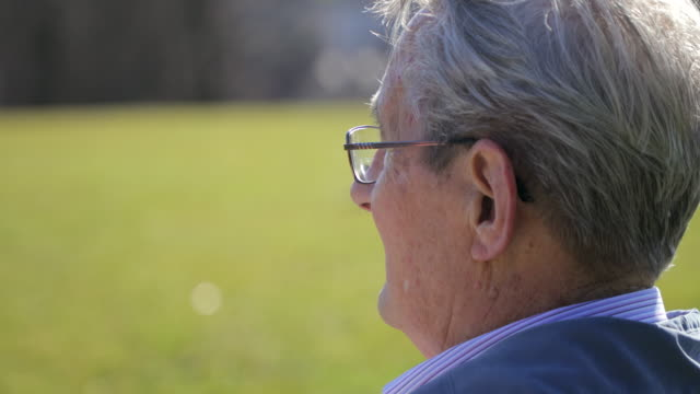 senior man sat alone on field looking into the distance - bench stock videos & royalty-free footage