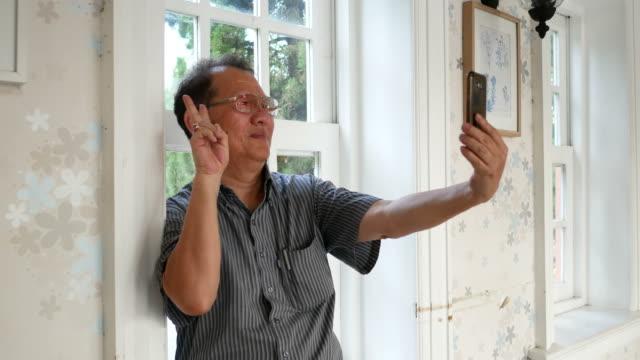 Senior woman Selfie von Smartphone mit Victory-Zeichen