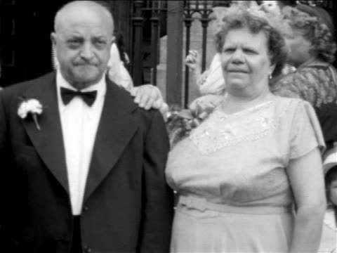 b/w 1955 home movie portrait senior man + senoior woman in formal wear standing of church at wedding - formal stock videos and b-roll footage