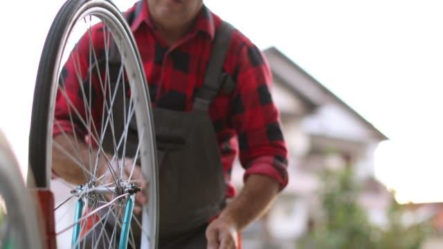 senior woman gewartet fahrräder - anweisungen konzepte stock-videos und b-roll-filmmaterial