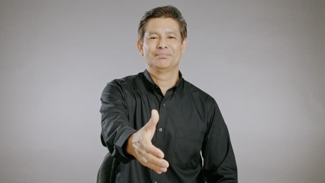senior man shake hand, big smile, talking, isolated in grey background. asian man in black shirt. - black shirt stock videos & royalty-free footage