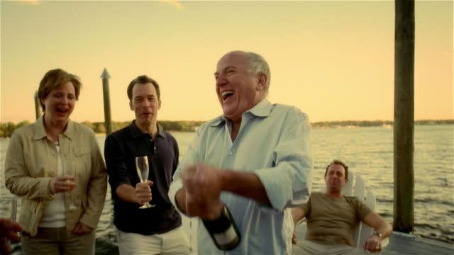 senior man shaking bottle of champagne as two men and one woman stand by holding champagne flutes on lakeside dock - in den fünfzigern stock-videos und b-roll-filmmaterial