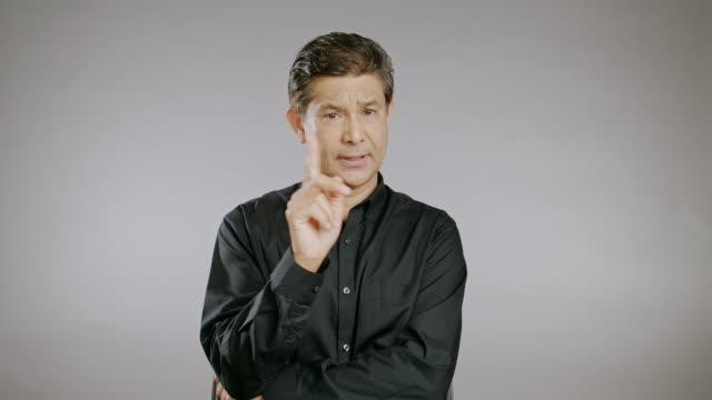 senior mann kopfschütteln, nein sagen, warnzeichen, unglücklich, großer kopfschütteln, isoliert im grauen hintergrund. asiatischer mann im schwarzen hemd. - vorderansicht stock-videos und b-roll-filmmaterial