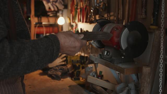 senior man sharpening machete in tool shed - workbench stock videos & royalty-free footage