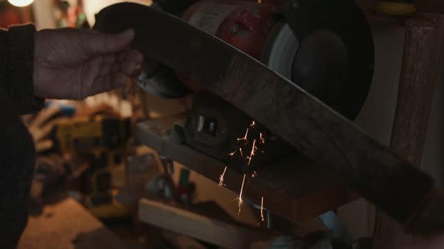 senior man sharpening machete in workshop - hobbies stock videos & royalty-free footage