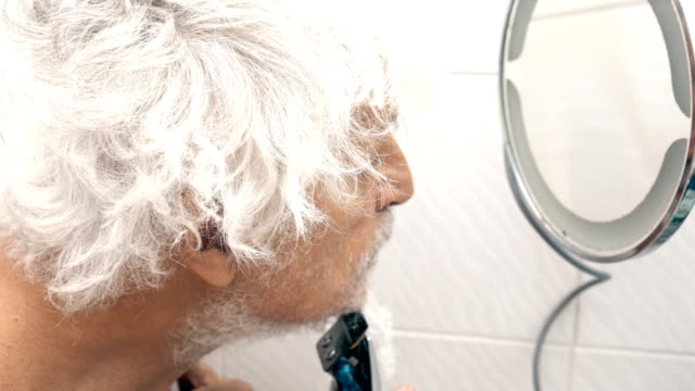vidéos et rushes de senior homme se rase au large de sa barbe - miroir ancien
