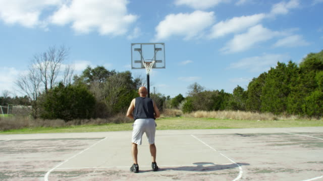 vidéos et rushes de senior man shooting free throws. - 55 59 ans