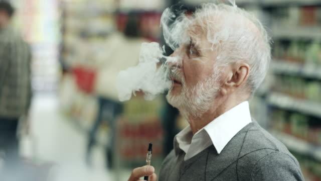 年配の男性がショッピングと vaping