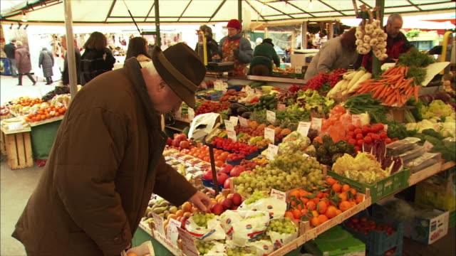 vidéos et rushes de ms senior man shopping for fruit in market / salzburg, austria - austria