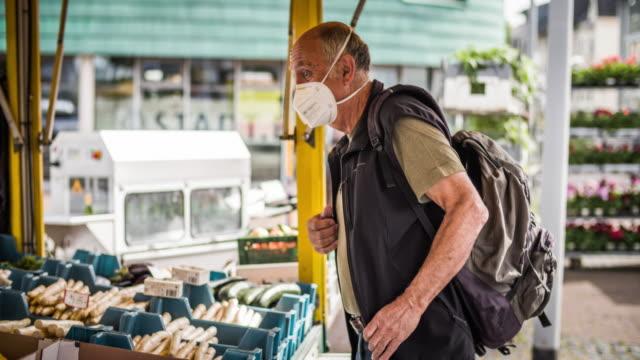 vídeos de stock e filmes b-roll de senior man shopping groceries  during coronavirus - covid-19 - mercado de produtos agrícolas