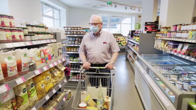 vidéos et rushes de homme aîné faisant du shopping dans le supermarché local pendant la pandémie - masque de chirurgien