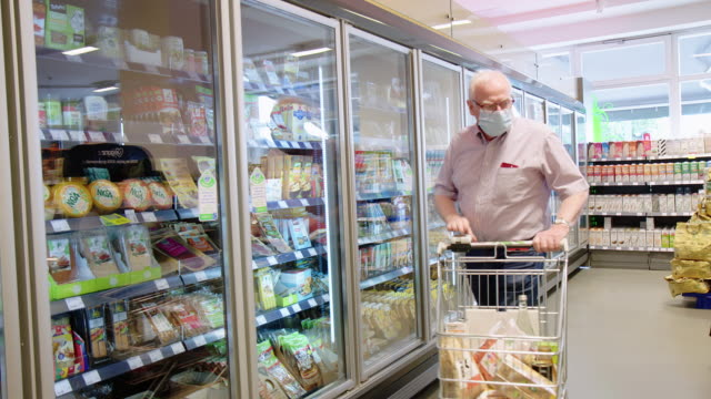 senior mann einkaufen im supermarkt während covid -19 pandemie - mundschutz stock-videos und b-roll-filmmaterial