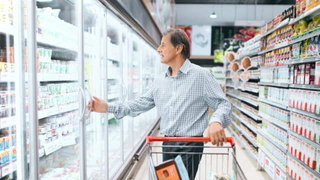 senior man shopping in supermarket - dairy product stock videos & royalty-free footage