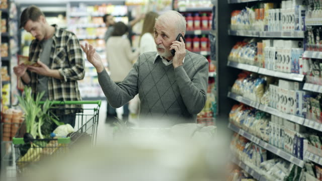 senior man shopping in supermarket - confusion stock videos and b-roll footage
