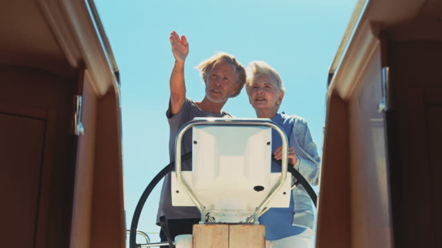 vídeos de stock e filmes b-roll de senior man showing direction to woman in yacht - guidance