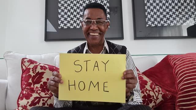 vídeos de stock, filmes e b-roll de idoso mostrando papel com 'stay home' escrito durante uma chamada de vídeo - ponto de vista da webcam - equipamento de mídia
