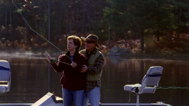 Senior man showing wife how to cast fly fishing line