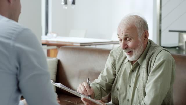 senior man signing financial papers - door to door salesperson stock videos & royalty-free footage