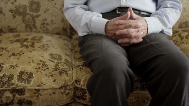 senior man sitting alone on a couch - loneliness stock videos & royalty-free footage