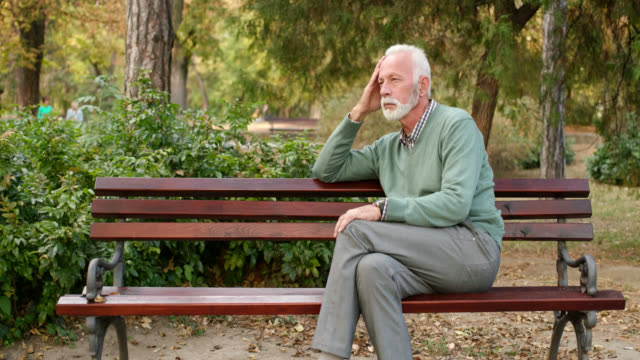senior man sitting alone on bench in the park - isolamento video stock e b–roll