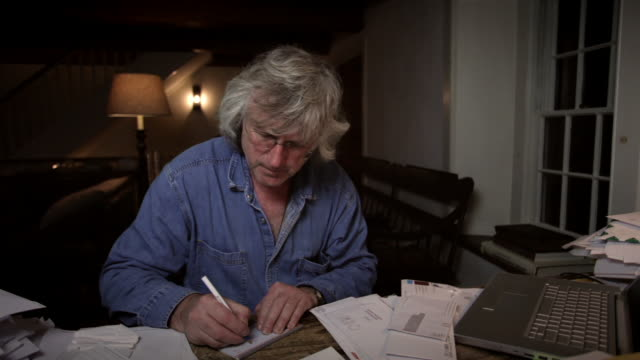 ms senior man sitting at desk late at night paying bills and balancing checkbook / kingston, new york, usa  - cheque financial item stock videos & royalty-free footage