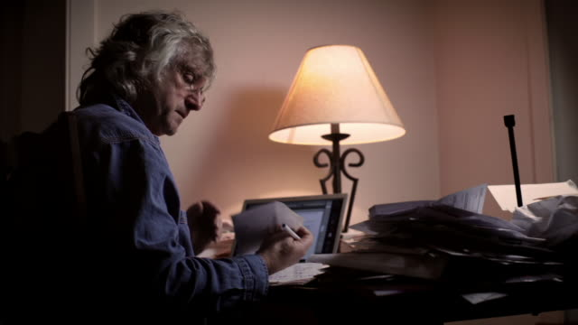 vídeos y material grabado en eventos de stock de ms senior man sitting at desk late at night paying bills / kingston, new york, usa  - lamer