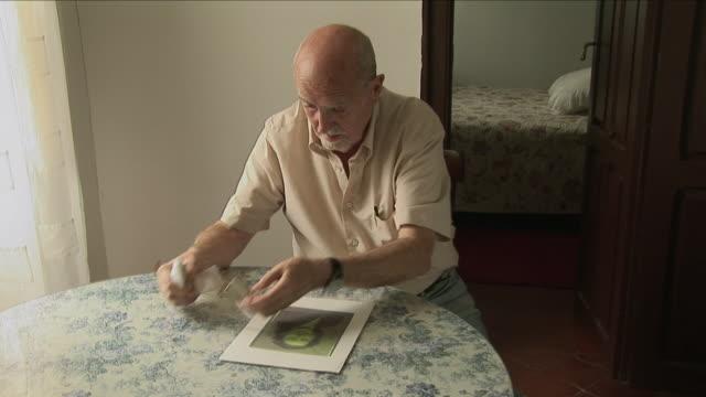MS Senior man sitting at table and looking at old photo of woman, Bilbao, Spain