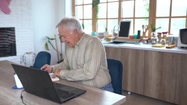 vidéos et rushes de homme aîné s'asseyant à la table et utilisant la loupe pour lire le livre à la maison - seniornaute