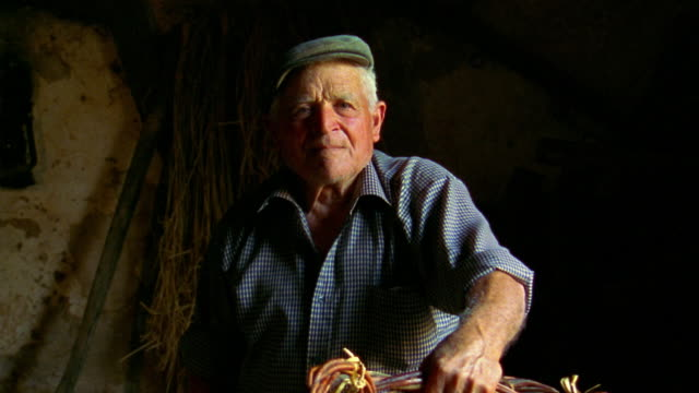 ms senior man sitting in barn with stern face / custonaci, sicily - lavoratore agricolo video stock e b–roll