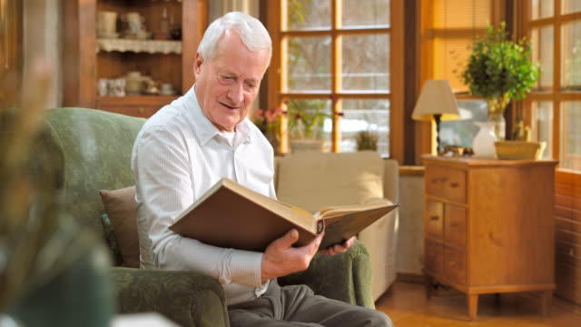 senior man sitting in chair and looking at photo album - photo album stock videos and b-roll footage