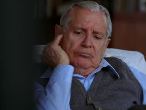 vidéos et rushes de senior man sitting in chair watching television / rubs his face - loneliness