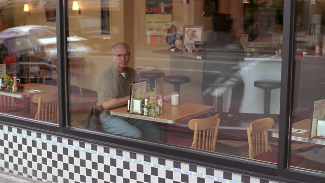 ws senior man sitting in diner while waitress pours his cup of coffee / seattle, washington, usa - seattle coffee stock videos and b-roll footage