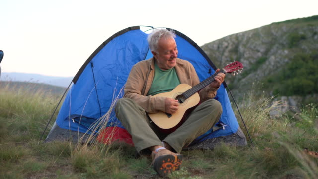 senior man sitting in front of tent and playing guitar while camping - adventure stock videos & royalty-free footage